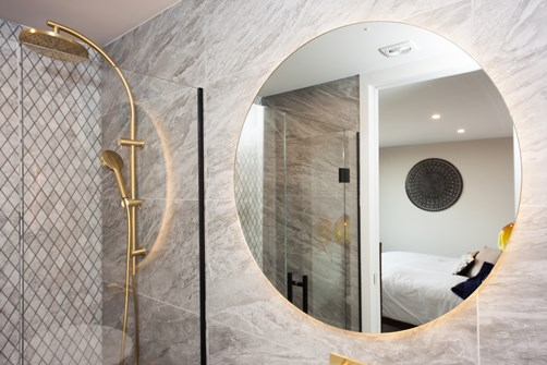 Metro Performance Glass 800mm diameter bathroom mirror with LED backlight and corner shower.jpg